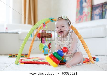 A little girl of 8 months, blonde hair tied with a white ribbon with a flower white rose, blue eyes, wearing a white T-shirt and panties, playing in the bright children's room on the floor with their many-colored toys on a white soft carpet