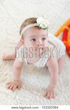 Cute little girl 8 months,blond hair tied with a white ribbon with a flower, white roses,blue eyes,dressed in a white t-shirt and panties,playing in the bright children's room on the floor on a soft fluffy white rug