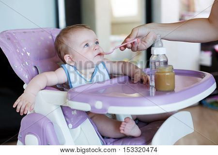 Cute baby with blond hair and blue eyes, wearing a blue shirt, sitting at a table purple for feeding babies, eating applesauce from pink spoon that feeds his mom