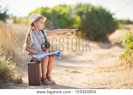 Cute little girl 6 years old,long hair braided into two pigtails,dressed in a summer Onesie blue color,on his head wearing a sun hat,behind wears light leather backpack,sitting on the old suitcase among the back roads,exploring the map of the area