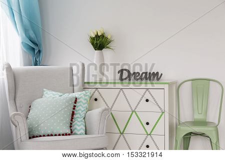 Shot of a white chest of drawers decorated with a washi tape mint chair and a comfortable armchair poster
