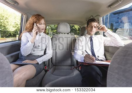 Businesspeople Sitting On A Backseat In A Taxi