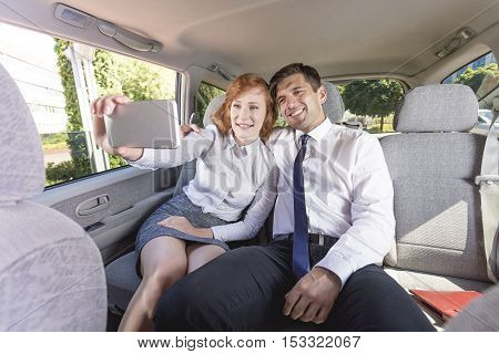 Businesspeople Taking A Selfie On A Backseat In A Taxi