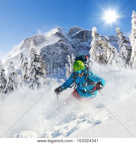 Freeride skier running downhill in freeze motion of snow powder.