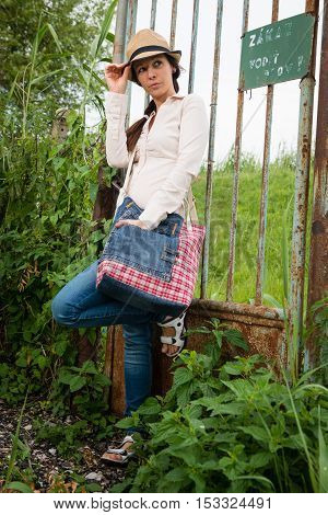 Portrait of young lady with handbag standing by the fence