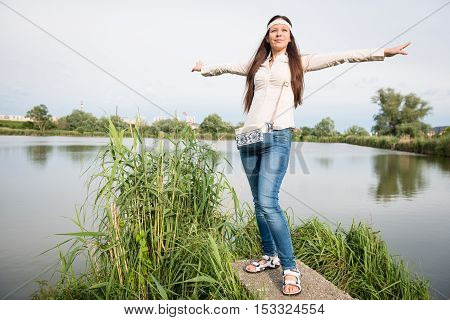 Portrait of young hippie lady in a jeans with handbag posing by the lake