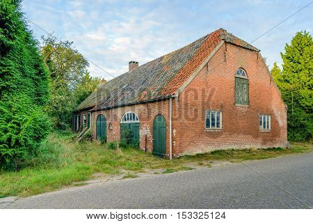 Abandoned and neglected historic long gable farmhouse built in 1885 in a small village in the Netherlands.