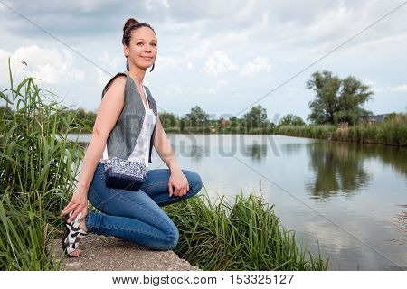 Portrait of young lady in jeans with handbag posing by the lake