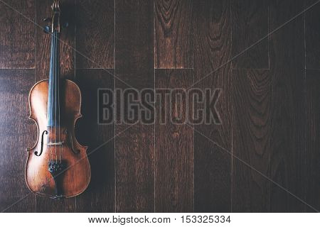 Top view of full length violin placed on wooden floor with copy space