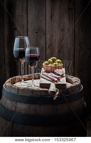 Tasty Red Wine In Glass With Olives And Cold Meats On Wooden Barrel
