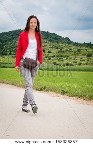 Portrait of young lady in red jacket walking on the road