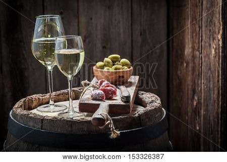 Chardonnay Wine With Olives And Cold Cuts On Old Barrel