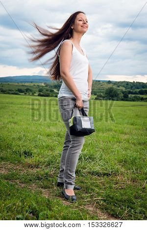 Portrait of young attractive lady with handbag posing on the meadow