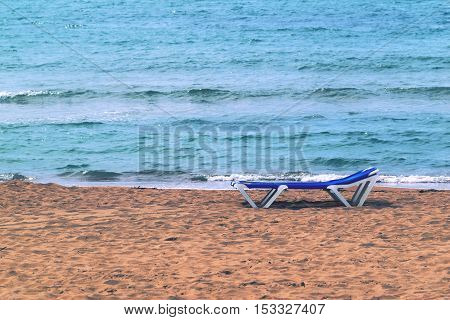 one isolated sunbed on the sandy coast and against the background of the sea