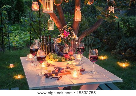 Beautiful Table Full Of Cheese And Meats In Garden At Dusk
