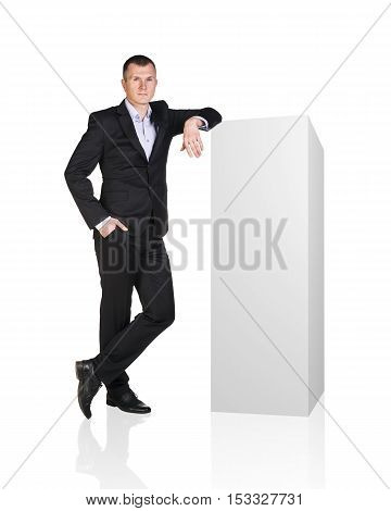 Hansome businessman leaned on white blank box. Presents product. Isolated on white