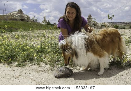 Young happy girl holding a dog which found a turtle in wildlife