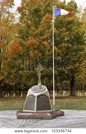 Caraquet, NB, October 17, 2016 -- Monument with NB Flag at Saint Anne Du Bocage Sanctuary on the outskirts of Caraquet shows off the bright fall colors on a slightly overcast but bright day in October.