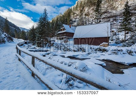 Frozen Mountain River And Wooden Cottage In Winter, Tatra Mountains, Poland