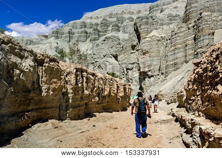 tourists are in the desert along the bed of a dry river