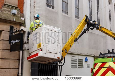 NOTTINGHAM ENGLAND - OCTOBER 22: Lighting services engineer working out of truck-based cherry picker on Low Pavement. In Nottingham England. On 22nd October 2016.