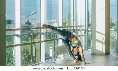 Woman stretching her leg at the barre.
