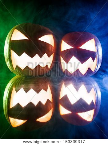 Two Glowing Pumpkins For Halloween On Blue And Green Light