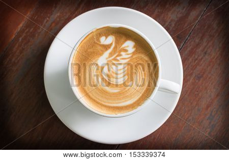 Top view coffee cup latte art on wood table.
