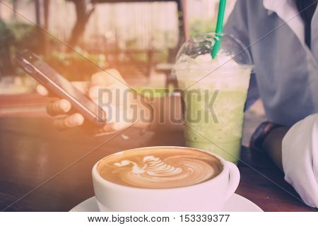 Women use mobile phone and drink green tea frappe with coffee cup vintage tone.