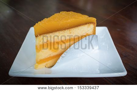 Cake orange on plate wood table in coffee shop.