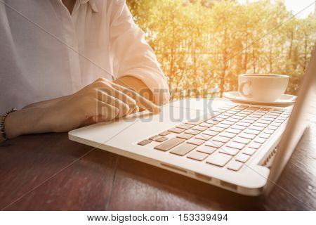 Women use laptop working with coffee cup in coffee shop vintage tone.