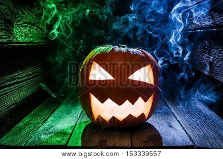 Glowing Pumpkins For Halloween With Blue And Green Smoke On Wooden Desk