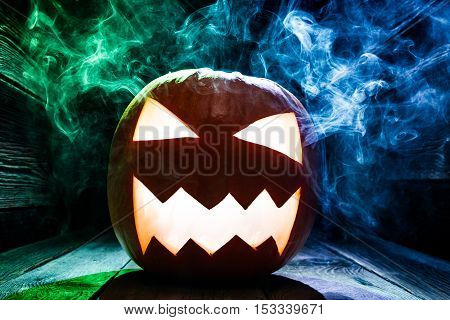 Closeup Of Pumpkins For Halloween With Blue And Green Smoke