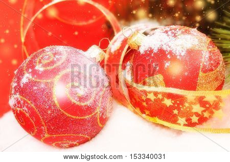 Two decorative red Christmas balls on a snowy scene