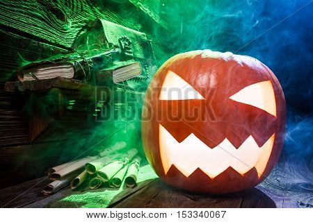 Scary Halloween pumpkin in witcher labolatory on old wooden table