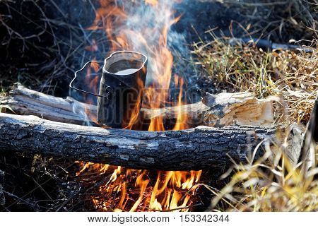 Smoked pot heating up on campfire on two logs