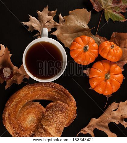 Cup of tea on the autumn fall leaves and pumpkin halloween mood