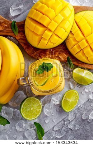 Healthy ripe Yellow Banana Mango Smoothie with slices of Lime, mint and ice.