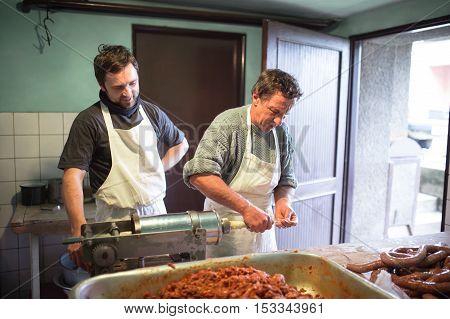 Two men making sausages the traditional way using sausage filler. Homemade sausage.