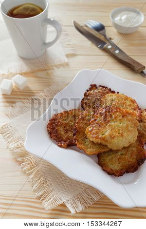 Potato pancakes on a white plate and a cup of tea