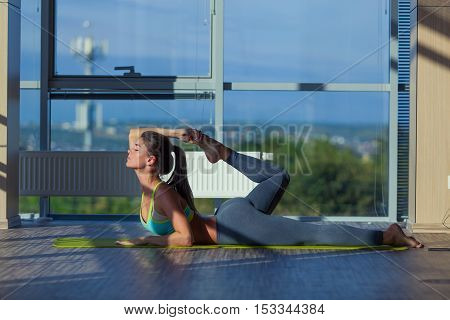 fitness, sport, training and lifestyle concept - smiling woman stretching on mat in gym. light from a large window