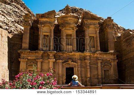 Photo of the Tourist woman in hat looking at monastery Ad Deir. Tourism concept. Travel and tourism concept
