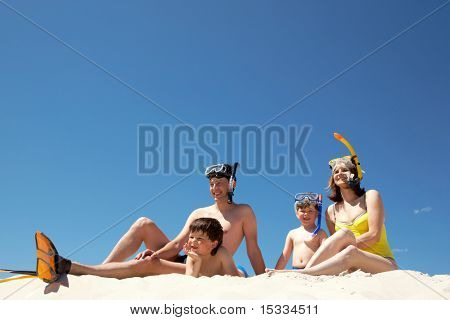 Portrait of modern family sitting on sandy beach against blue sky