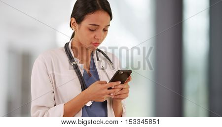 Latina doctor texting on smartphone in the hallway