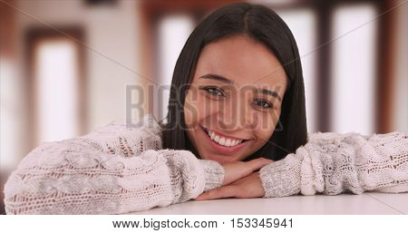 Cute Mexican girl smiling at camera and lying on desk