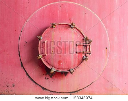 Red old and rusty manhole of storage tank. Entry to confined space tank.