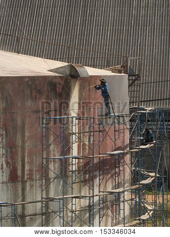 Worker cleaning storage tank by air pressure sand blasting in high position.