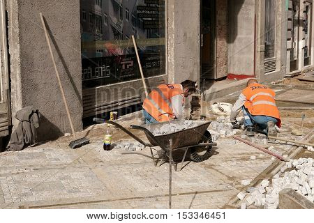 PRAGUE, CZECH REPUBLIK - OCTOBER 20, 2016: Construction workers renovate a walkway with paving stones in the city centre of Prague.