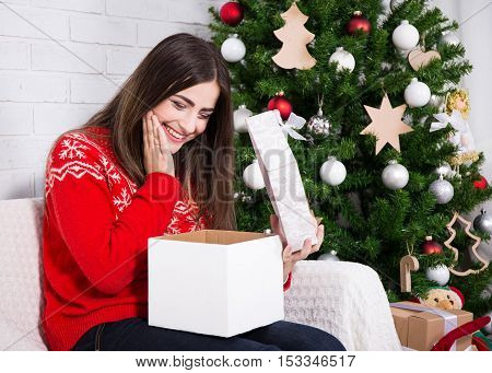 Happy Surprised Woman Opening Gift Box Near Decorated Christmas Tree