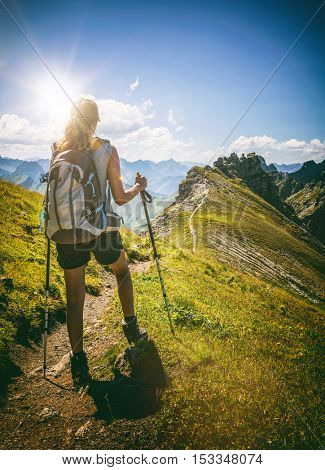 Strong female hiker with backpack pauses on path to take in the scenic view of majestic mountain range